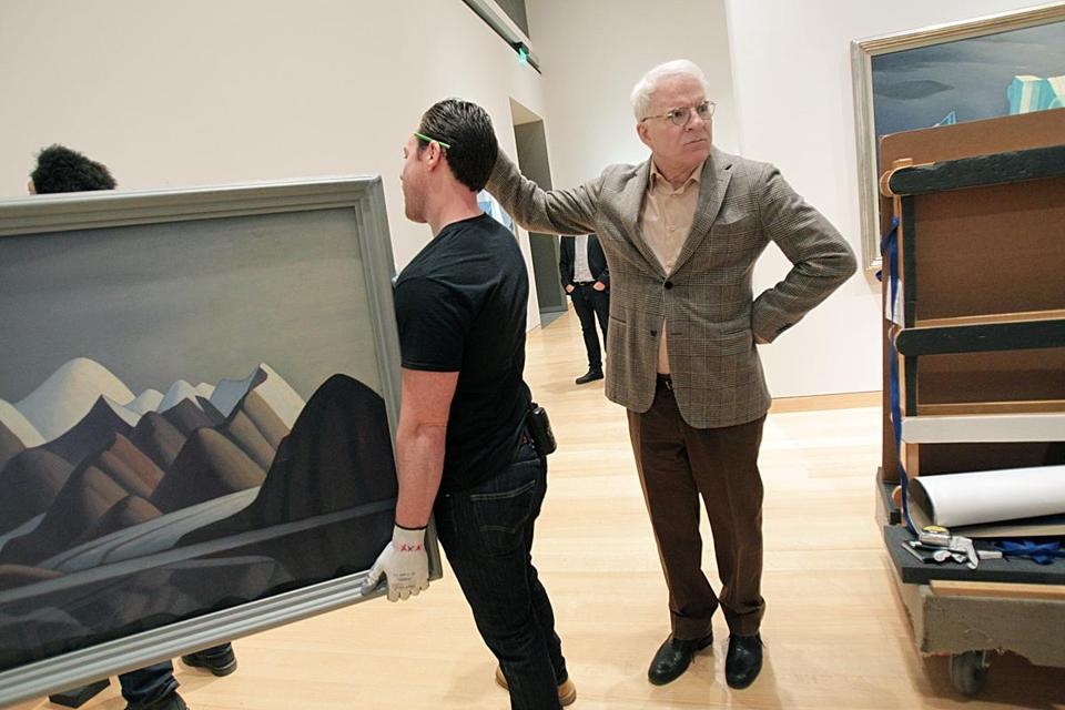 Steve Martin watched the paintings of Lawren Harris go into place Tuesday at the Museum of Fine Arts. He traveled widely to museums in Canada to collect the works.